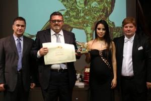 La consegna del Leone d'Oro al dott. Leopoldo Marzano da parte del presidente Candelaresi. Con loro, i conduttori Gabriele Marconi e Luz Adriana Sarcinelli