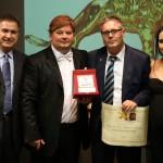 Il presidente Candelaresi premia il titolare Stefano Lo Verso, insieme ai conduttori Gabriele Marconi e Luz Adriana Sarcinelli