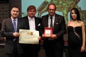 Il presidente Candelaresi conferisce la Targa d'Oro al titolare Vincenzo Mangiapia, insieme ai conduttori Gabriele Marconi e Luz Adriana Sarcinelli