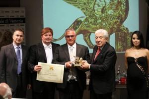 Il dott. Arbib consegna il Leone d'Oro a Fabrizio Roncella, alla presenza del dott. Sileno Candelaresi e dei conduttori Luz Adriana Sarcinelli e Gabriele Marconi